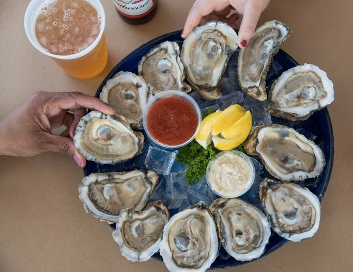 close up of oysters on platter with hands holding two of them and beers